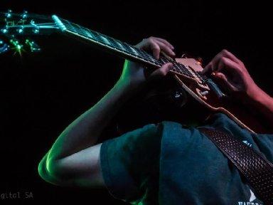 Joe playing guitar behind head 1